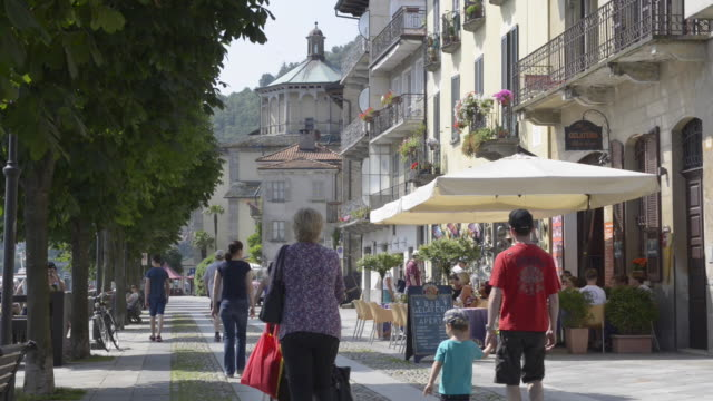 People and street cafe at lakeside promenade of Cannobio
