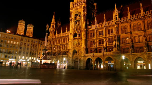 people and traffic move through the plaza in front of neues rathaus in marienplatz, munich, germany. - rathaus stock videos & royalty-free footage
