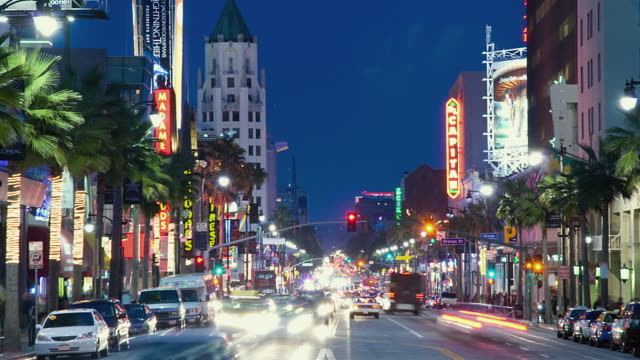 WS ZI T/L People and traffic on Hollywood Boulevard at dusk / Hollywood, California, USA