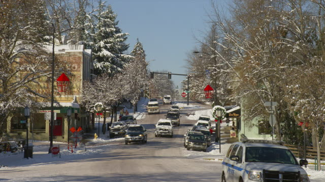 vídeos de stock e filmes b-roll de wide zoom out people and traffic on snowy street in downtown ashland, oregon - lugar genérico