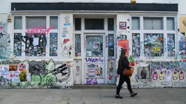people and traffic pass a derelict building covered in graffiti and street art, brick lane - poster stock videos & royalty-free footage
