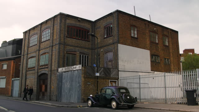 vidéos et rushes de people and traffic pass vintage black cab and brick building - hackney