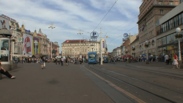 ws people and trolleys in ban jelacic, zagreb's main square / zagreb, croatia  - trolleybus stock-videos und b-roll-filmmaterial