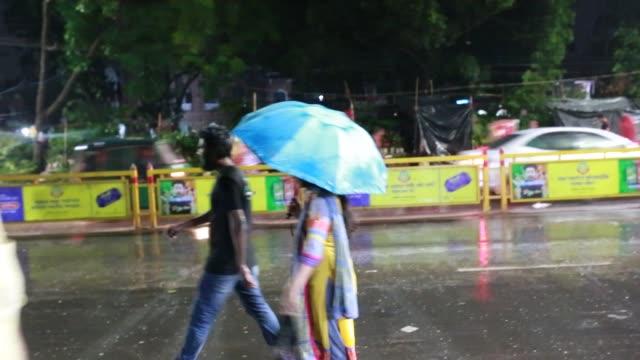 people and vehicle on street during sudden rain in dhaka, bangladesh on april 11, 2018. - 水の形態点の映像素材/bロール