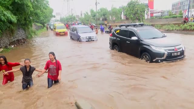 people and vehicles wade through a flooded street after heavy monsoon rains in jakarta, indonesia on february 20, 2017. - monsoon stock videos & royalty-free footage