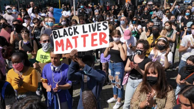 "people applaud as a man in the crowd holds a sign saying ""black lives matter"" during a protest rally against racism following the recent death of... - demonstrant stock-videos und b-roll-filmmaterial"