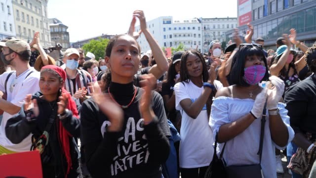 "people applaud as a woman in the crowd wears a t-shirt saying ""black lives matter"" during a protest rally against racism following the recent death... - demonstrant stock-videos und b-roll-filmmaterial"