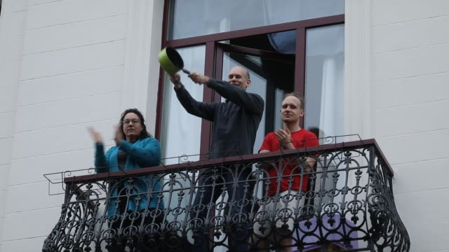 vídeos y material grabado en eventos de stock de people applaud from their balconies doctors and nurses for all their hard work during the coronavirus pandemic on april 4, 2020 in brussels, belgium.... - ovacionar