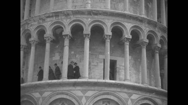 people approach the door to the tower a few men walk along its floors with a slow pan to the top of the structure/ an elevated view of pisa cathedral... - pisa cathedral stock videos & royalty-free footage