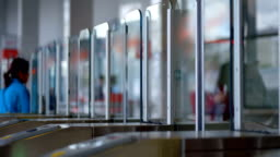People approach to the metro turnstiles with glass doors, the doors open
