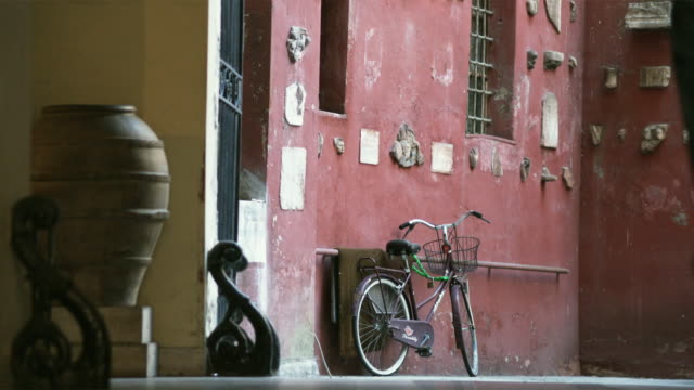 vidéos et rushes de ms people approaching building, bike leaning on wall / rome, italy - plan de situation