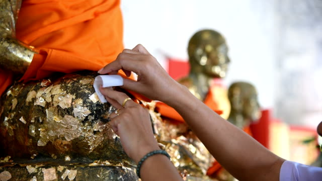 people are applying a piece of gold leaf on buddha statue - gold leaf stock videos & royalty-free footage