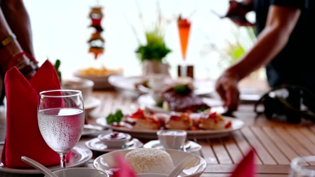 people are arranging variety food on wooden dining table in tropical sea - seafood stock videos & royalty-free footage