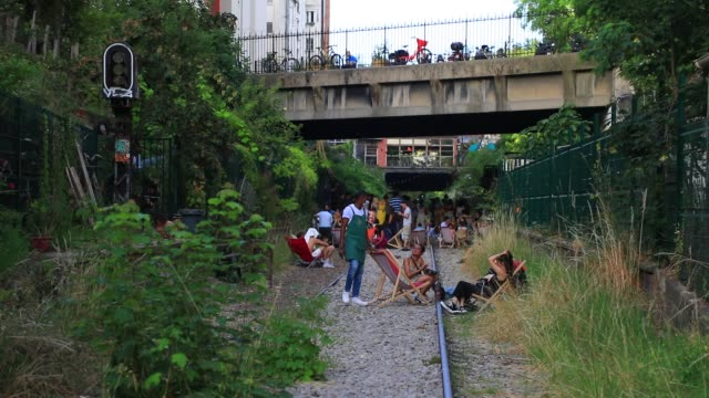 people are chatting in deckchairs during a sunny summer afternoon at the paris former small belt railway on july 19 2020 in paris france left fallow... - cool attitude stock videos & royalty-free footage