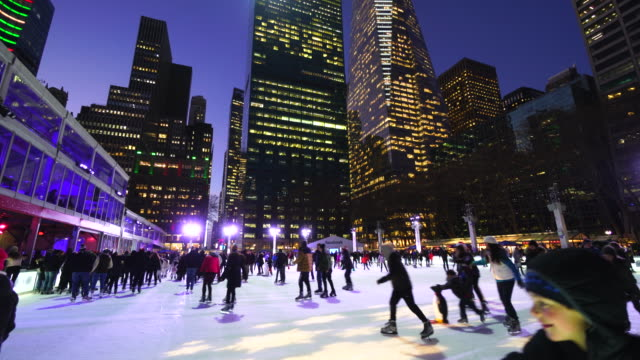 people are enjoying ice skating at bryant park new york in dusk at christmas holidays season on dec. 20 2016. - bryant park stock videos & royalty-free footage