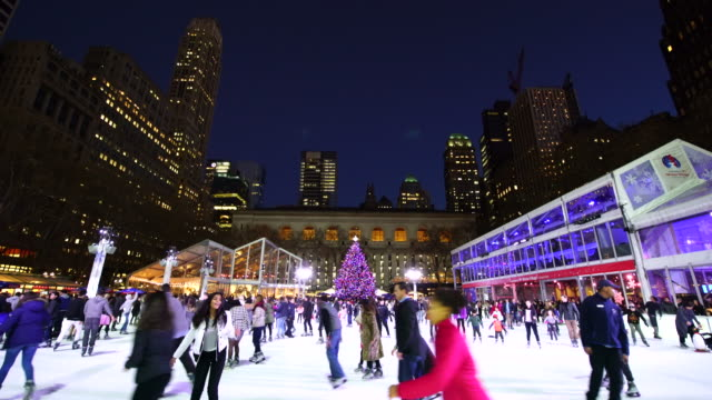 people are enjoying ice skating at bryant park new york in dusk at christmas holidays season on dec. 27 2016. a christmas tree stands at front of new york city library. - bryant park stock videos and b-roll footage