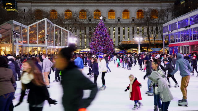people are enjoying ice skating at bryant park new york in dusk at christmas holidays season on dec. 28 2016. a christmas tree stands at front of new york city library. - bryant park stock videos and b-roll footage