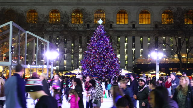 vídeos de stock e filmes b-roll de people are enjoying ice skating at bryant park new york in dusk at christmas holidays season on dec. 27 2016. a christmas tree stands at front of new york city library. - patinagem no gelo