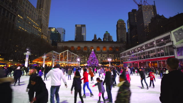 people are enjoying ice skating at bryant park new york in dusk at winter holidays season on jan. 01 2017. a christmas tree stands at front of new york city library. - bryant park stock videos & royalty-free footage