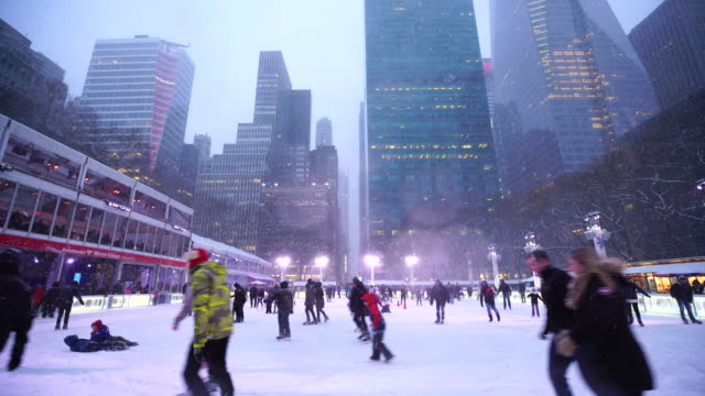 people are enjoying ice skating during snowing at bryant park new york in dusk at christmas holidays season on jan. 10 2017. - public celebratory event stock videos & royalty-free footage