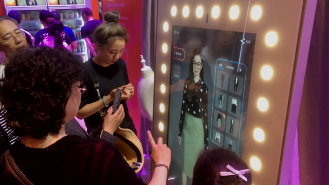 People are experiencing the AI fitting technology while shopping on Tmallcom or Taobaocom in the future Alibaba shows its smart technology in...