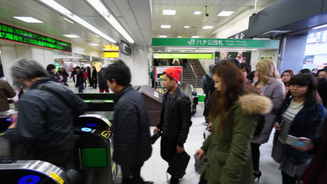 people are going through the automatic ticket gate at hachiko entrance shibuya station on sunday evening. - 地下鉄駅点の映像素材/bロール