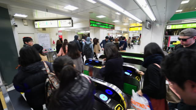 people are going through the automatic ticket gate at hachiko entrance shibuya station on sunday evening. - station点の映像素材/bロール