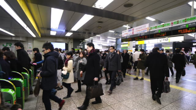 People are going through the automatic ticket gate at Shibuya Station.