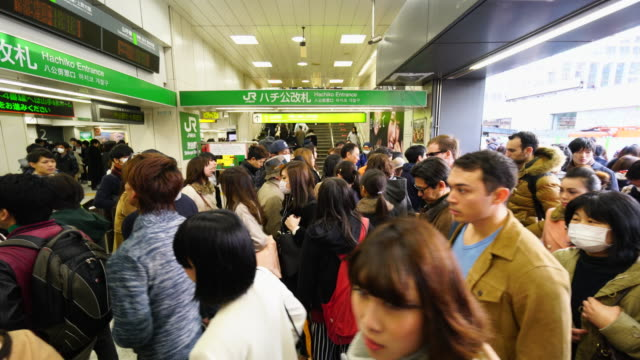 people are going to the automatic ticket gate at hachiko entrance shibuya station on sunday evening. - 地下鉄駅点の映像素材/bロール