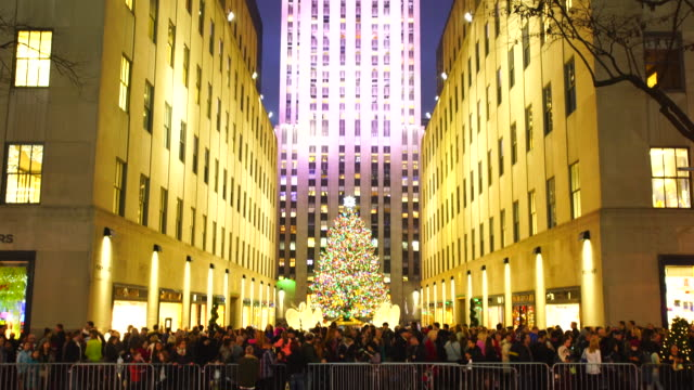 people are moving on the sidewalk and watching saks fifth avenue christmas light show from opposite side of 5th avenue. - rockefeller center christmas tree stock videos & royalty-free footage
