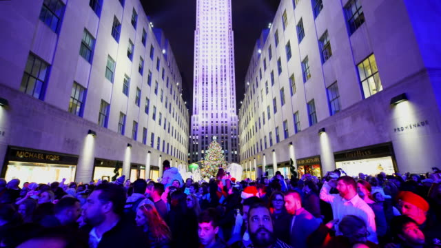 people are moving on the sidewalk and watching saks fifth avenue christmas light show from opposite side of 5th avenue. - albero di natale del rockefeller center video stock e b–roll