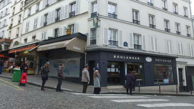 vidéos et rushes de people are queueing with a meter distance between them in front of a bakery on rue coustou, 75018 paris. president macron announced on monday march... - file d'attente