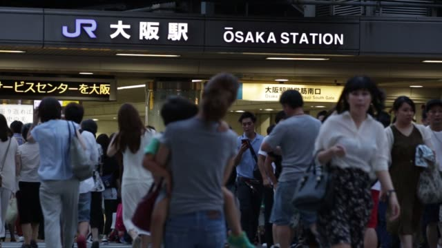 people are reflected in a glass wall while signage for osaka station is displayed in osaka, japan, on saturday, june 18 pedestrians walk past signage... - 大阪駅点の映像素材/bロール