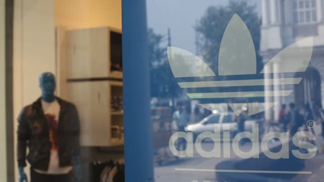 people are reflected in an adidas originals sign at an adidas ag store in connaught place in new delhi new delhi street scenes on february 22, 2013... - adidas stock videos & royalty-free footage