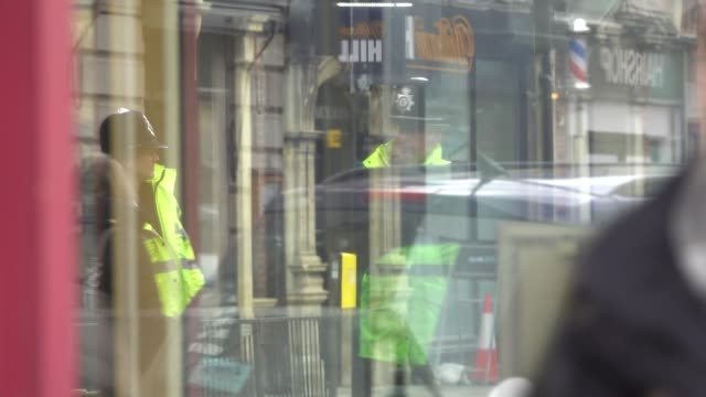people are reflected in shop windows as police officers continue to stand guard outside the nearby zizzi restaurant in salisbury, as police and... - wiltshire stock videos & royalty-free footage