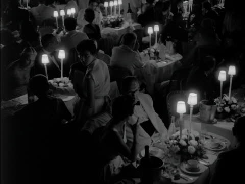 People are seated for dinner in a hotel in Monte Carlo 1950s