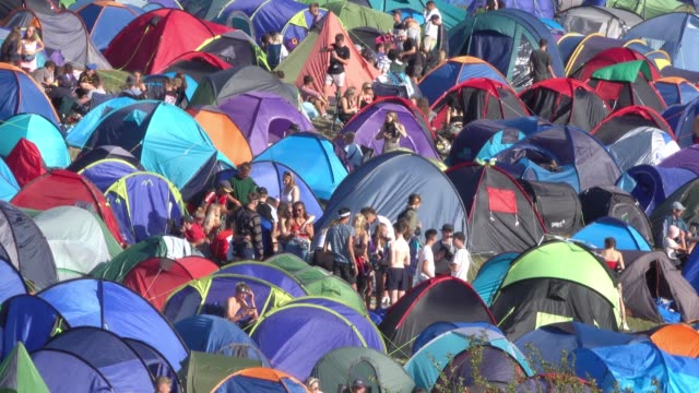 stockvideo's en b-roll-footage met people are seen amongst tents pitched at the annual boardmasters music festival at watergate bay on august 10, 2018 in cornwall, england. since 1981,... - festivalganger