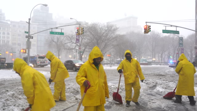stockvideo's en b-roll-footage met people are shoveling snow at union square on 14th street during the snowstorm in the morning on mar. 14 2017. - extreem weer