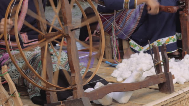 People are silk weaving in Thailand.