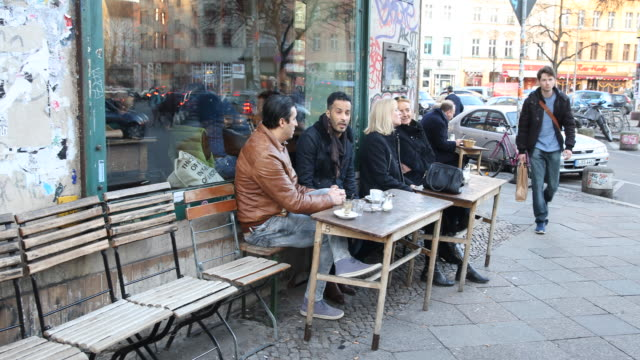 people are sitting in front of a cafe / bar in oranien street at the heinrichsplatz a famous nightlife area and multi culture district with a lot of... - cafe culture stock videos and b-roll footage