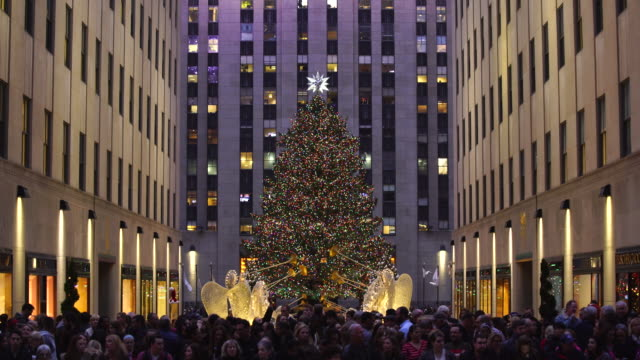 people are waiting for beginning of saks fifth avenue christmas light show from opposite side of 5th avenue - rockefeller center christmas tree stock videos & royalty-free footage