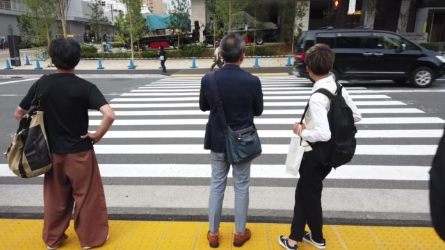 people are waiting on traffic light in front the tokyo national stadium. fifty-six years after having organised the olympic games, the japanese... - segnale per macchine e pedoni video stock e b–roll