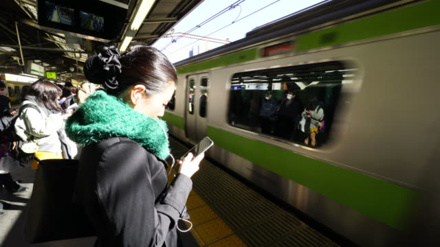 people are waiting to get on to the yamanote line. - 待つ点の映像素材/bロール