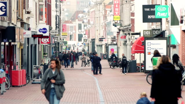 stockvideo's en b-roll-footage met people are walking around in the early hours of the day on a shopping street in leiden, the netherlands. - stadsweg