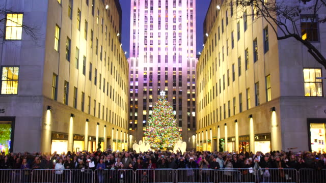 people are watching saks fifth avenue christmas light show from opposite side of 5th avenue. - rockefeller center christmas tree stock videos & royalty-free footage