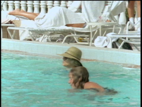 people around and in swimming pool at resort in st petersburg florida - stereo personale video stock e b–roll