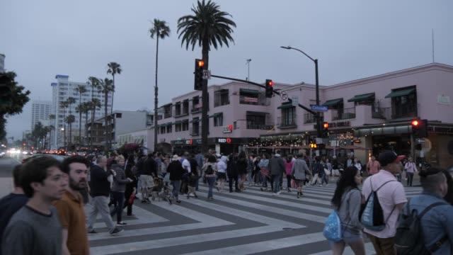 people around entrance to santa monica pier at dusk, santa monica, los angeles, california, united states of america, north america - santa monica sign stock videos & royalty-free footage