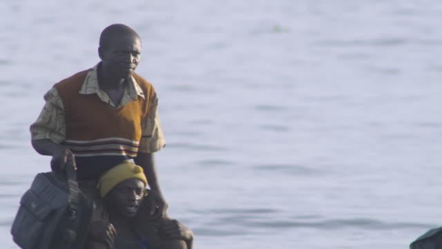 vidéos et rushes de ms pan people arriving by boat being carried ashore at lakeshore / buikwe, uganda - inondation