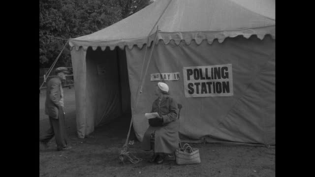 stockvideo's en b-roll-footage met people arriving to vote at polling station in a tent at hounslow cricket ground in the 1955 general election - 1955