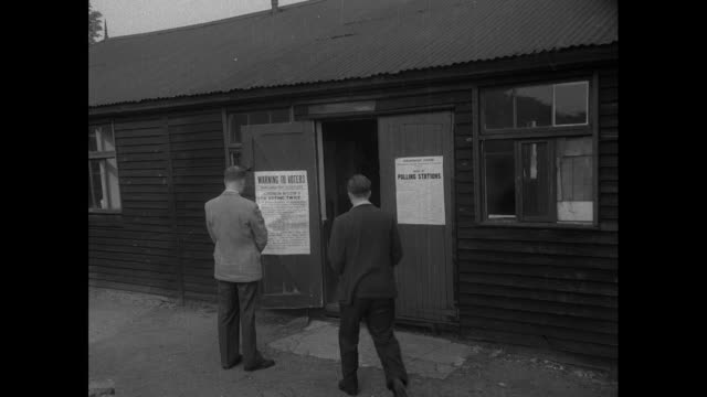 stockvideo's en b-roll-footage met people arriving to vote in a polling station located in a shed in 1955 general election - 1955